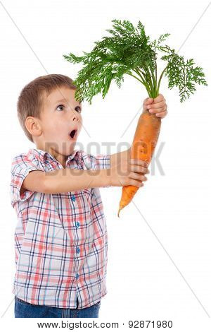Amazed boy with big carrot