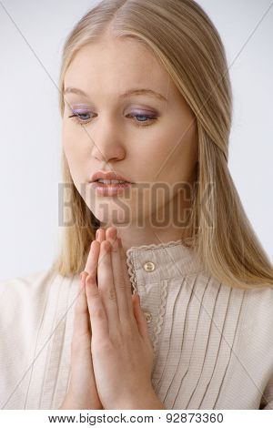 Young blonde woman praying, looking down.