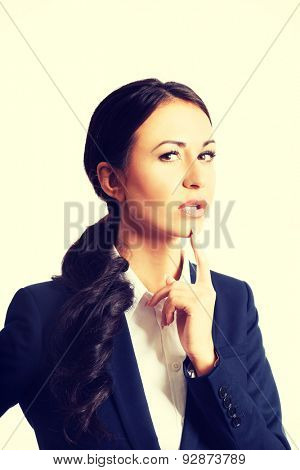 Portrait of thoughtful businesswoman with a finger under chin looking at the camera.