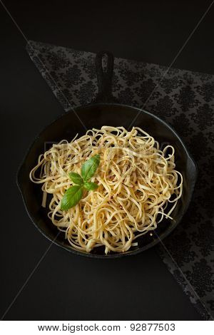 Linguine In A Cast Iron Pan With Basil On Black Background