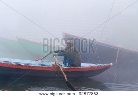 Indian Man Sailing On The Boat On Sacred River Ganges At Cold Foggy Winter Morning