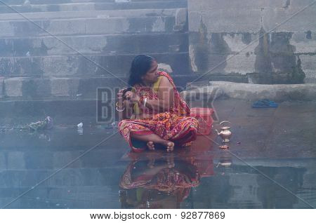 Indian Woman Taking Ritual Bath In The River Ganges At Cold Foggy Winter Morning. Varanasi
