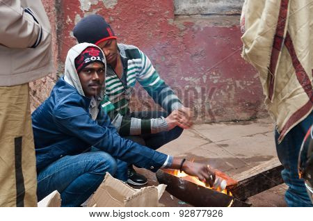 Indian Men Heating Themselves At The Fire At Cold Foggy Winter Morning. Varanasi