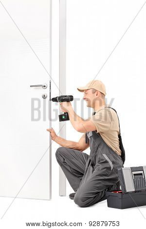 Vertical shot of a cheerful male locksmith installing a door lock with a hand drill isolated on white background