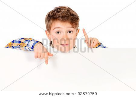 Cute boy stands behind a white board. Copy space. Isolated over white.
