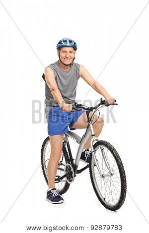 Full length portrait of a senior with a blue helmet posing seated on a bicycle isolated on white background