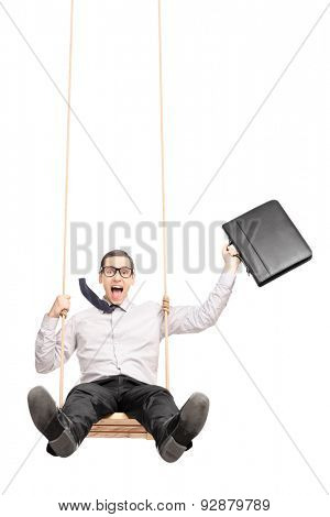 Vertical shot of an excited businessman holding a briefcase and swinging on a swing isolated on white background