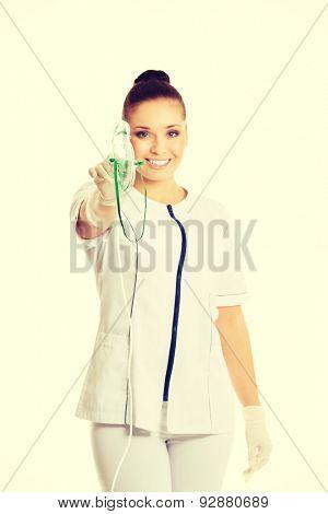 Female doctor holding up oxygen mask.