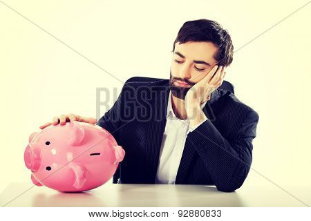 Worried businessman with piggybank by a desk.