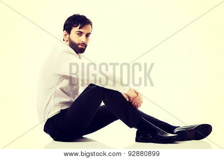 Young happy businessman sitting on the floor.