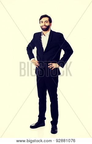 Smiling confident businessman with hands on hips.