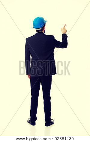 Businessman engineer with hard hat pointing up.