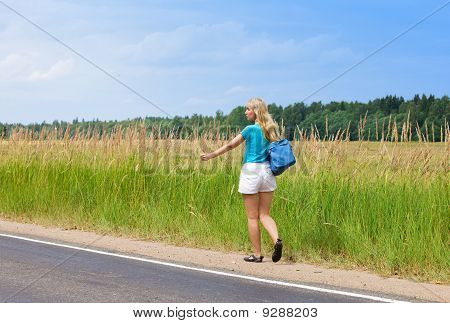 """Beautiful young woman hitch hiking- in auto-stop """"votes"""" on road"""