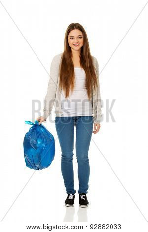 Happy young woman holding a full garbage bag.