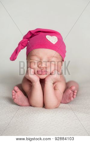 Newborn Baby Girl Wearing A Pink Top Knot Cap