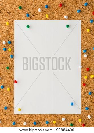 White Paper Note Sheet With Multicolored Push Pin On Cork Board