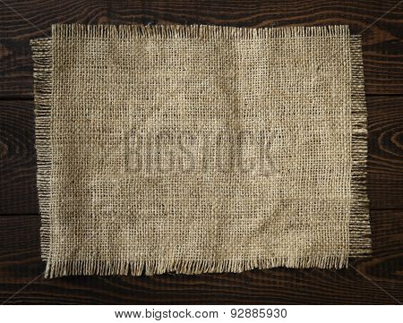 Hessian cloth on a wooden background