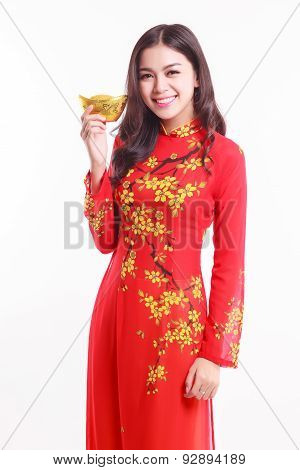 Beautiful Vietnamese Woman With Red Ao Dai Holding Lucky New Year Ornament - Stack Of Gold On White