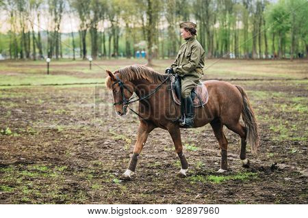Unidentified woman re-enactor dressed as Soviet soldier ride on