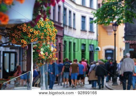 Tourists Walking Along The Street Of The Old Town With Flowers In Cafe