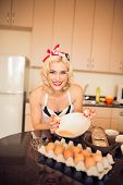 pic of scrambled eggs  - Portrait of attractive housewife scrambling eggs at home - JPG