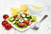 foto of radish  - Spring salad with tomato cucumbers and radish on a wooden background