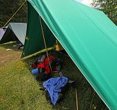 stock photo of boy scout  - big tent of boy scout camp with backpacks and sleeping bags spread out - JPG