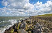 stock photo of wind-farm  - Wind farm in water along a dike in spring - JPG