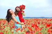 image of preteens  - Mother and her 7 years old preteen child playing in spring flower field - JPG