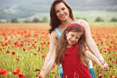 image of preteen  - Mother and her 7 years old preteen child playing in spring poppy field in soft sunlight - JPG