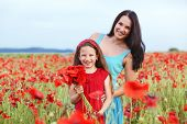 stock photo of 7-year-old  - Mother and her 7 years old preteen child playing in spring flower field - JPG