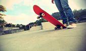 stock photo of skateboard  - closeup of young skateboarder legs and skateboard at  skateparks - JPG