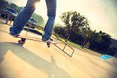 picture of skateboard  - skateboarder legs riding on skateboard at skatepark ramp - JPG