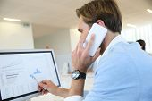 image of negotiating  - Bank trader negotiating on the phone from office - JPG