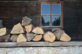 picture of log cabin  - Logs on a porch of an old village house with a window behind - JPG