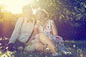 stock photo of flirt  - Romantic couple in love flirting on grass in sunny spring park - JPG
