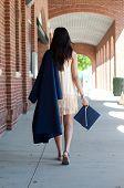 stock photo of girl walking away  - Teen graduate girl walking away from camera wearing robe - JPG