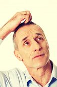 picture of scratching head  - Mature confused man scratching his head - JPG