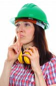 stock photo of silence  - Female construction worker wearing green helmet and protective headphones holding finger to lips and showing silence sign safety at work and ear protection - JPG