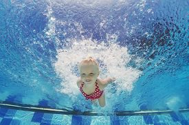 stock photo of child development  - Baby girl swimming underwater and diving in pool with fun  - JPG