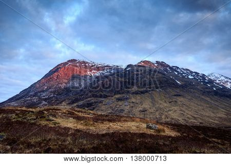 with the sun setting behind me the peaks of this mountain light up red. Glencoe Scotland UK.