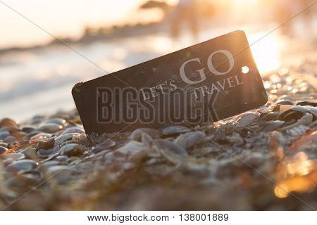 Lets go travel, adventure motivation concept, tag on the beach with text