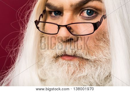 old bearded professor man wizard in glasses with blue lenses in eyes with long gray beard and white hair has emotional serious face on purple background portrait