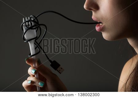 female mouth with sexy lips holding with finger usb flash wire cable for connection and white plastic fork on grey background closeup