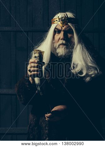 old druid bearded man with long beard on serious face and hair in fur coat and crown with gem stones jewellery on wooden background holding animal antler or horn