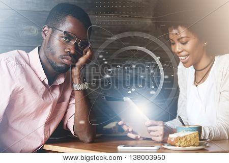 Double Exposure Of African Man In Glasses Sitting At A Cafe With Bored Look While His Stylish Girlfr