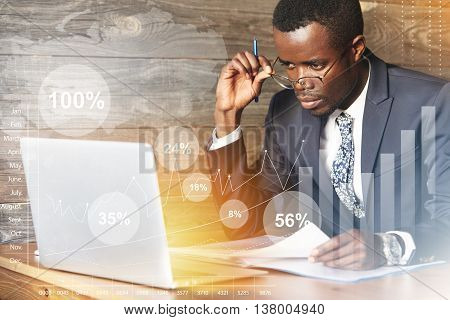 Serious African Businessman Looking At Laptop Screen, Studying A Financial Report, Doing Paperwork W
