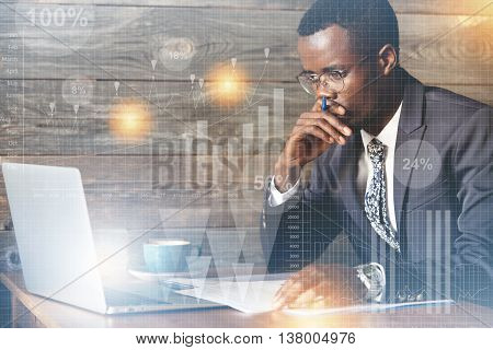 Visual Effects. Serious African Businessman In Spectacles Looking At The Laptop Screen With Thoughtf