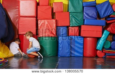 Sad child sitting in corner of gym and boy tries to comfort him