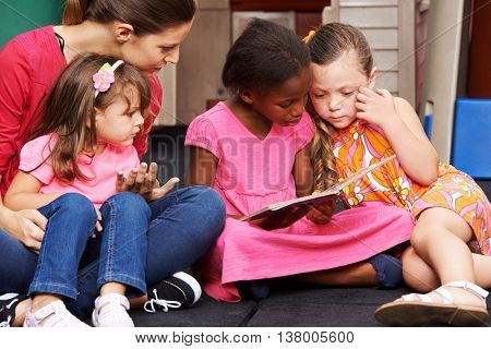Group of children and educator with picture book in a kindergarten